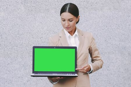 Portrait young beautiful business woman in suit look at empty green screen with copy space on laptop on gray background. Attractive happy girl entrepreneur hold computer with green chroma key in hands
