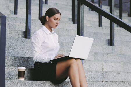 Young attractive girl student in suit sit on stairs and use laptop and drink coffee outdoors. Beautiful confident business woman typing keyword on computer on city street. Busy freelance entrepreneur
