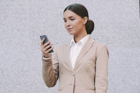 Portrait happy beautiful millennial girl entrepreneur hold mobile phone in hand and smile on gray background. Young attractive business woman use smart phone. Successful female corporate lawyer.