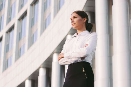 Portrait young attractive confident business woman in suit keep arms crossed and look away near office building. Beautiful girl corporate lawyer with crossed arms. Professional entrepreneur, girl boss Standard-Bild