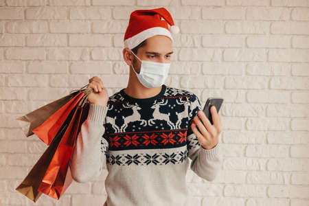 Happy festive man in Santa hat, protective face mask hold stay home banner in hands. Cheerful young man in Christmas sweater show stay home advice. Home quarantine, winter holidays, social awareness