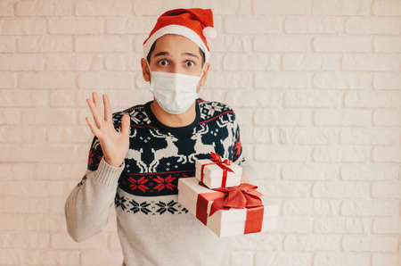 Young male doctor in Santa hat, medical face mask, protective gloves hold red heart in hands. Happy man surgeon in protective face mask show heart sign with fingers. Christmas donation, charity, help