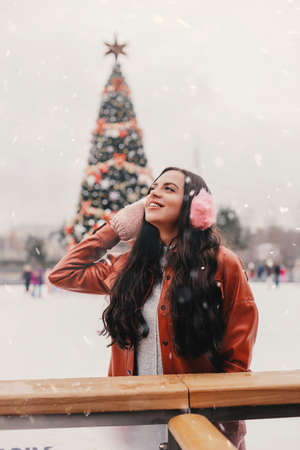 Portrait pretty young happy woman in stylish jacket, pink earmuffs skate on outdoor Christmas ice rink. Beautiful cheerful girl have fun and smile on ice skating rink. Winter holidays season activity