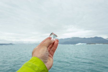 Peice of melting glacier ice in mans hand on Iceland, summer, 2015