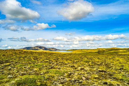 Panoramic view of illuminated grass field and waterfall on Iceland, summer time, wide angle, sunny day, South Iceland