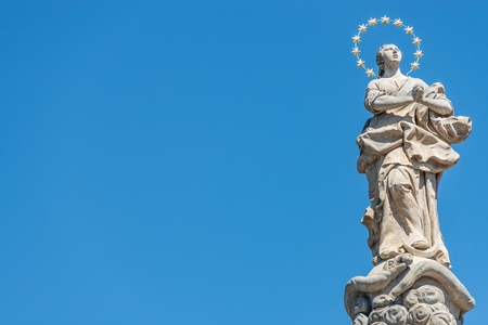 Statue of praying lady at Marian Column or Holy Trinity at Hradcanske Square for bubonic plague epidemics in Prague, Czech Republic, portrait, details, blue sky Stock Photo