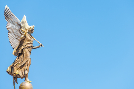 Statue of beautiful angel with wings in front of the Rudolfinum concert hall in Prague, Czech Republic, portrait, details, blue sky Editorial