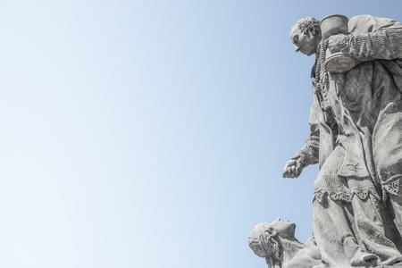 Praga, República Checa: estatuas en la columna mariana o Santísima Trinidad en la plaza Hradcanske para las epidemias de peste bubónica en Praga, República Checa, retrato, detalles, cielo azul degradado