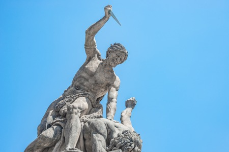 PRAGUE, CZECH REPUBLIC:Statue of Battling Titan with a dagger at the main Gate of Hradcany Castle in Prague, Czech Republic, blue sky, sunny day Editorial