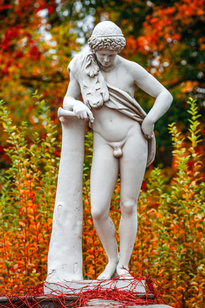 Statue of sensual renaissance era Roman man in lion skin with hunting tube at golden Autumn, Potsdam, Germany Stock Photo