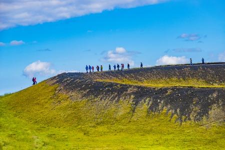 Tourists at the top of pseudo craters aka volcanic near Skutustadir and lake Myvatn on Iceland Редакционное