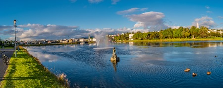 Panoramic view of Reykjavik downtown with lake on Iceland during sunset with rainbow