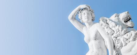 Banner einer alten Statue der sinnlichen Renaissance-Ära-Frau, die auf großen Löwen mit blauem Himmelsverlaufshintergrund in Potsdam, Deutschland, legt Standard-Bild