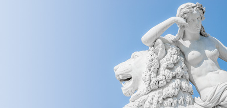 Banner of an ancient statue sensual Renaissance Era woman laying on big lion with blue sky gradient background in Potsdam, Germany Stock fotó