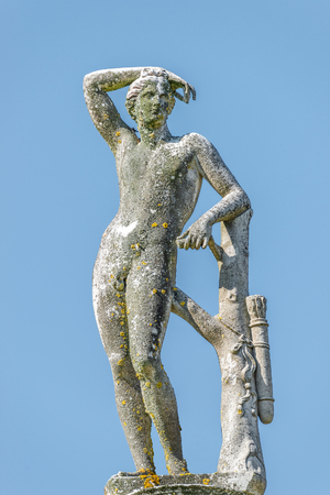 Ancient statue covered with moss and lichen of a hunter in Potsdam, Germany, details, closeup