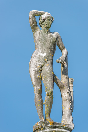 Ancient statue covered with moss and lichen of a naked hunter in Potsdam, Germany, details, closeup