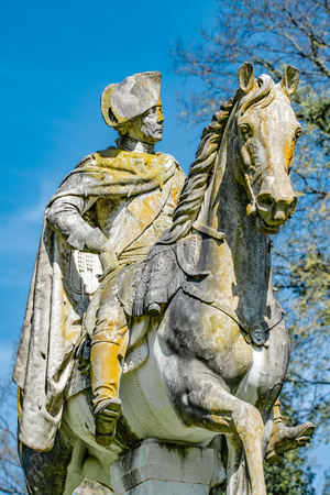 Very old statue of Prussian King Frederick the Great covered with moss and lichen, Potsdam, Germany, details, closeup