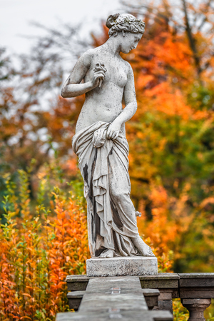 Statue of sensual naked Roman renaissance era woman with flowers at golden Autumn, Potsdam, Germany Stock Photo