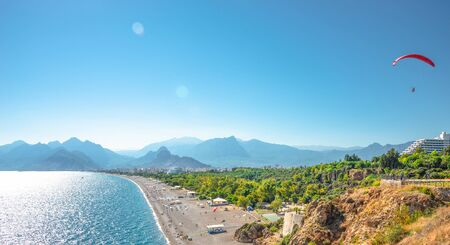 Panoramic bird view over Antalya and Mediterranean seacoast, beach and mountains with free flying paraglider, Antalya, Turkey, sunny day, blue sky