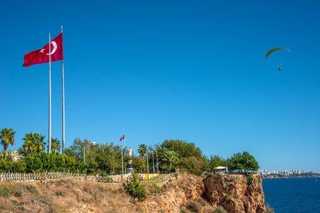 Bird view of Antalya and Mediterranean seacoast and beach with a paraglider and Turkish flag, Antalya, Turkey, Summer