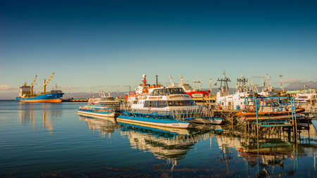 Cargo and cruise tour ships at Ushuaia harbor in Tierra del Fuego National Park at sunset, Patagonia, Argentina