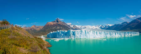 Panoramic view at the huge Perito Moreno glacier in Patagonia with hikers, South America, Argentina, sunny day, blue sky Stok Fotoğraf