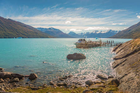 Panoramic view over turquoise water glacial lagoon from gigantic Perito Moreno glacier in Patagonia with a tour boat and tourists boarding it, South America, Argentina, at sunny day