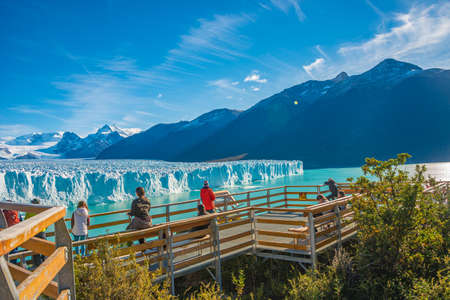 Famous Perito Moreno glacier and mountain turquoise lagoon with austral forests at golden Autumn in Patagonia, with tourists watching the glacier at the lookout platform, Argentina