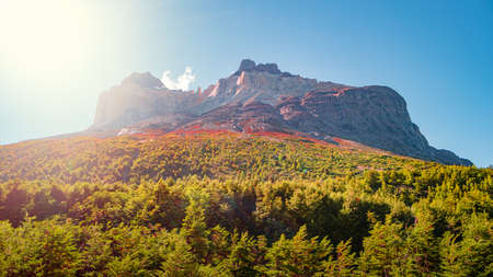 Magical colorful sunrise at major peaks, standing high towers teeth, and waterfall nearby surrounded by wet austral forests in Torres del Paine National Park, Patagonia, Chile Stok Fotoğraf