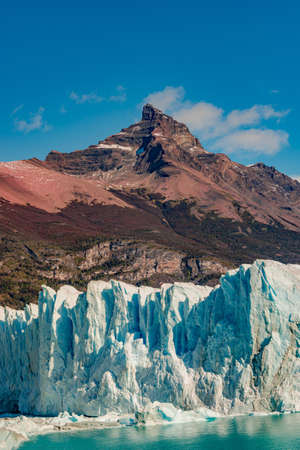 Famous Perito Moreno glacier and mountain turquoise lagoon with austral forests at golden Autumn in Patagonia, South America, Argentina at sunny day and blue sky Stok Fotoğraf