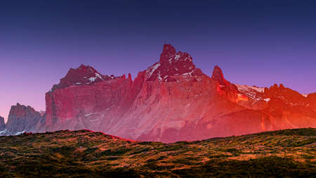 Magical colorful sunrise at major peaks, standing high towers teeth, and waterfall nearby surrounded by wet austral forests in Torres del Paine National Park, Patagonia, Chile