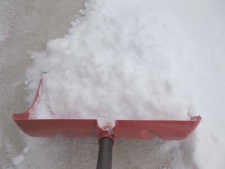 Snow shovel shoveling snow close-up Reklamní fotografie