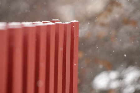 Blurred photo of snow falling by red fence