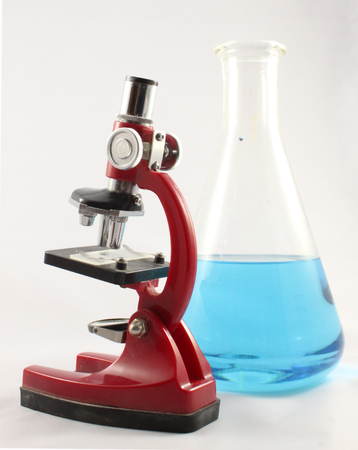 Red light microscope and Erlenmeyer flask with blue liquid isolated on white background Zdjęcie Seryjne