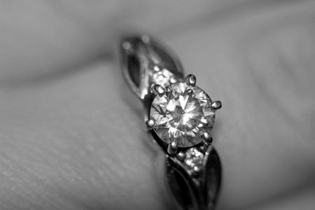 Diamond ring on finger in black and white