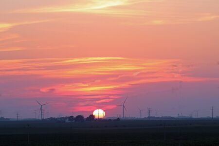 Sunset sky with wind turbines on the horizon