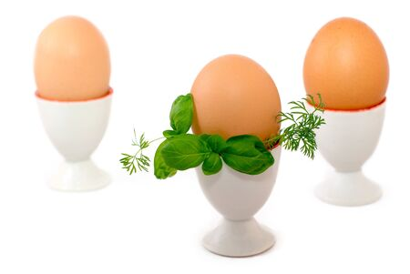 Eggs in eggcups isolated, decorated with greenery photo