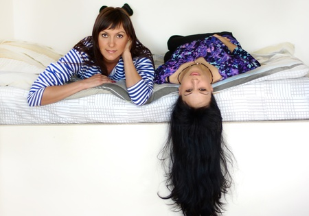 black hairs: Two girlfriends, laying on the bed, long black hairs Stock Photo