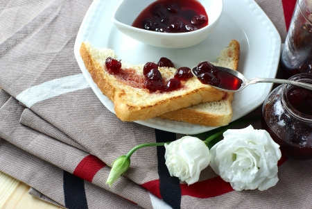 Sweet cherry jam, toast and white flowers photo