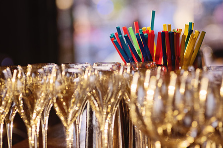 champagne glasses and multicolor cocktail straws