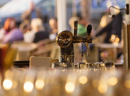 Dispenser voor het afgeven bier op. Outdoor café, bar op de achtergrond. Blured glinsterende voorgrond, ondiepe scherptediepte