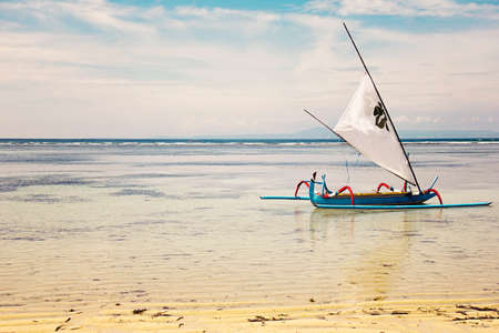 Exotic seascape with traditional Jukung boat on the water, Bali, Indonesia