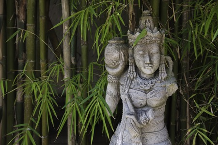Traditional Balinese stone sculpture in bamboo forest at Bali,  Indonesia