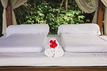 sun beach: Spa bungalow, inner view. White matraces and white towels with exotic flower
