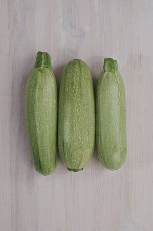 marrow squash: Three whole squashes on light background. Soft natural lighting. View from top.
