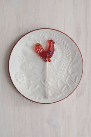amber coloured: Sugar cockerel on white decorated dish. Common sweet in eastern Europe countries, especially in Latvia, Lithuania, Estonia an Russia.