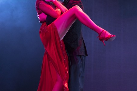 tangoing: Two dancers performing tango in blue and red stage lights. Close up view of legs, no faces.