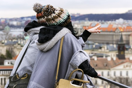Two unrecognizable women look at the Prague city from the hill.