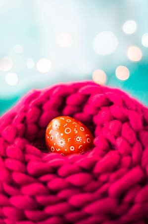 Easter egg in the knitted wool nest Easter decor.