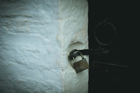 Hinged metal black lock hangs on a rusty metal flask attached to a wooden panel and fixed with metal handle on the other side of metal door.